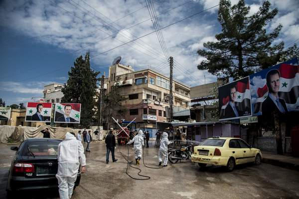 FILE - In this March 24, 2020 file photo, workers spray disinfectant to prevent the spread of the coronavirus, on a street lined with billboards showing Syrian President Bashar Assad, in Qamishli, Syria. (AP Photo/Baderkhan Ahmad, File)