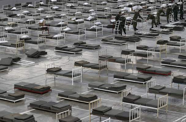 In this March 24, 2020, photo, Serbian soldiers set up beds for treatment of possible COVID-19 infected patients inside of the Belgrade Fair, Serbia. (AP Photo/Darko Vojinovic)