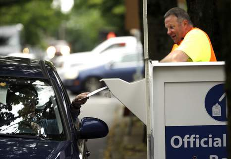 Election 2020 Vote by Mail FILE - In this May 16, 2016, file photo election worker Randy Polivka watches as a motorist drops off their ballot at a ballot drop box site in Portland, Ore. (AP Photo/Don Ryan, File) (Don Ryan