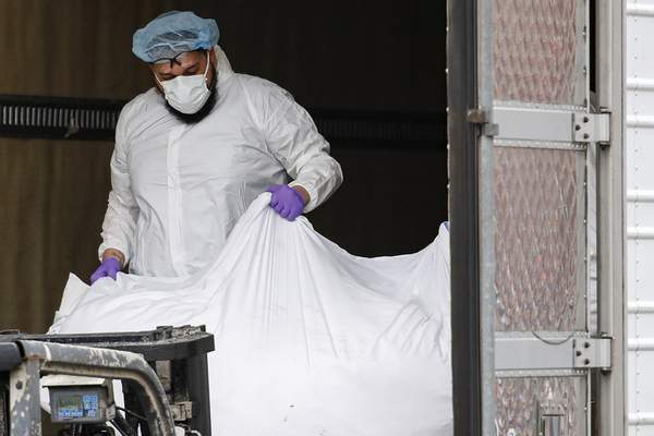 Associated Press A body wrapped in plastic is loaded onto a refrigerated container truck used as a temporary morgue Tuesday at Brooklyn Hospital Centerin New York.