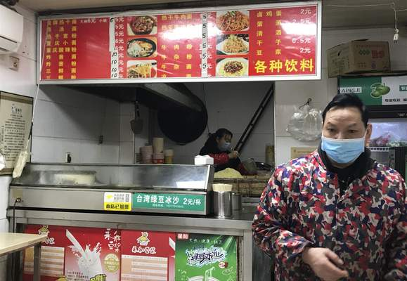 """Associated Press Workers at a store selling reganmian, or """"hot dry noodles,"""" prepare takeaway orders Tuesday in Wuhan, China."""
