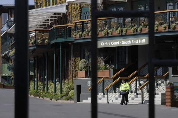 A security guard inside the main gates to Wimbledon as it is announced the the Wimbledon tennis Championships for 2020 has been cancelled due to the coronavirus in London, Wednesday, April 1, 2020. (AP Photo/Kirsty Wigglesworth)