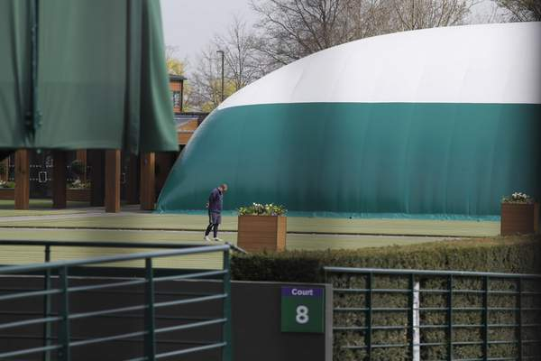 A groundsman looks at the grass on one of the outside courts at Wimbledon as it is announced the the Wimbledon tennis Championships for 2020 has been cancelled due to the coronavirus in London, Wednesday, April 1, 2020. (AP Photo/Kirsty Wigglesworth)