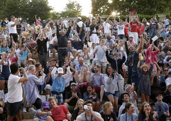 FILE - In this Friday, July 12, 2019 file photo, people sitting on Murray mound celebrate after the Switzerland's Roger Federer defeated Spain's Rafael Nadal in the men's singles semifinal match on day eleven of the Wimbledon Tennis Championships in London. (AP Photo/Tim Ireland, File)