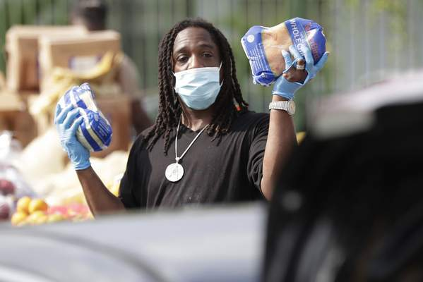 Associated Press Terry Axson Jr. holds up two chickens as he waits for the next car to pass during a food distribution event Wednesday in the Liberty City neighborhood of Miami.