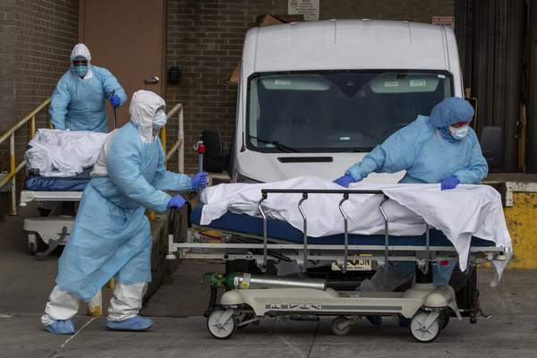 Medical personnel wearing personal protective equipment remove bodies from the Wyckoff Heights Medical Center Thursday, April 2, 2020 in the Brooklyn borough of New York. (AP Photo/Mary Altaffer)