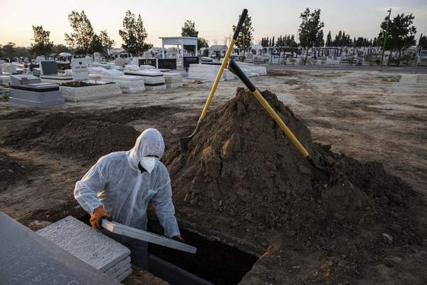Member of Hevra Kadisha, an organization which prepares bodies of deceased Jews for burial according to Jewish tradition, prepares the grave before a funeral of a Jewish man who died from coronavirus in the costal city of Ashkelon, Israel, Thursday, April 2, 2020. (AP Photo/Tsafrir Abayov)