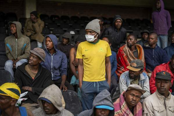 Homeless people stay at the Caledonian stadium downtown Pretoria, South Africa, Thursday April 2, 2020, after being rounded up by police in an effort to enforce a 21 day lockdown to control the spread of the coronavirus. (AP Photo/Jerome Delay)