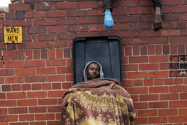 Henry sits in a bin as he and other homeless people rest at the Caledonian stadium downtown Pretoria, South Africa, Thursday April 2, 2020, after being rounded up by police in an effort to enforce a 21-day lockdown to control the spread of the coronavirus. (AP Photo/Jerome Delay)