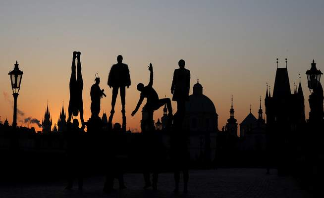 Street artists are silhouetted against the rising sun as they perform on the near empty Charles Bridge in Prague, Czech Republic, Thursday, April 2, 2020. (AP Photo/Petr David Josek)