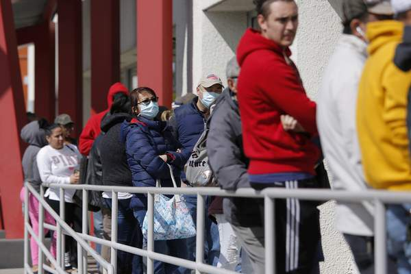 FILE - In this March 17, 2020 file photo, people wait in line for help with unemployment benefits at the One-Stop Career Center in Las Vegas. (AP Photo/John Locher)