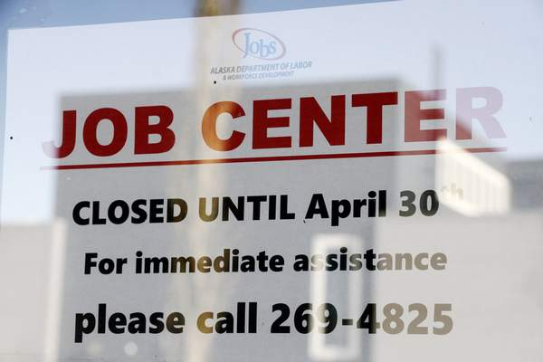 In this March 30, 2020 photo, a sign saying that the Jobs Center at the Alaska Department of Labor and Workforce Development office in midtown Anchorage, Alaska, is closed through the end of April is shown. (AP Photo/Mark Thiessen)