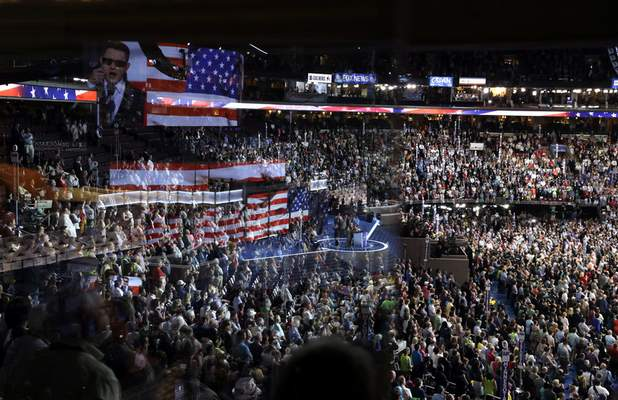 FILE - In this July 26, 2016, file photo the stage is reflected on a glass window on the suite level at Wells Fargo Arena as Timmy Kelly sings the national anthem before the start of the second day session of the Democratic National Convention in Philadelphia. The coronavirus pandemic is forcing Democrats and Republicans to take a close look at whether they'll be able to move forward as planned this summer with conventions that typically kick off the general election season. (AP Photo/John Locher, File)