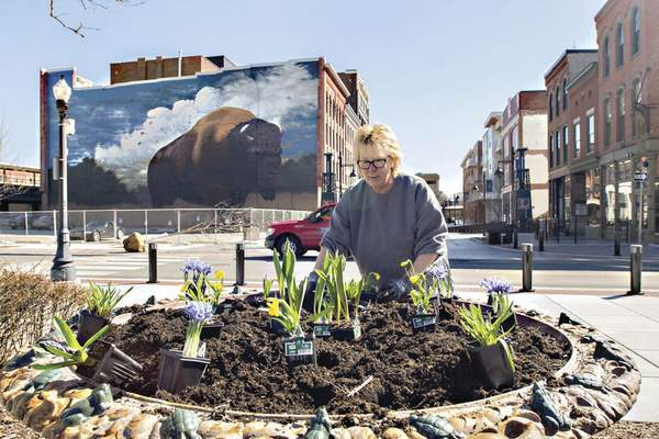 Michelle Davies | The Journal Gazette Penny Hundley, a resident at Randall Lofts, takes advantage of the warmer temperatures to plant flower containers outside the apartment Thursday morning.