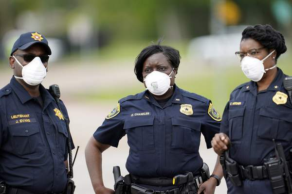 Associated Press Law enforcement officers wear masks Thursday while working at a newly opened free drive-thru COVID-19 testing site in Houston.