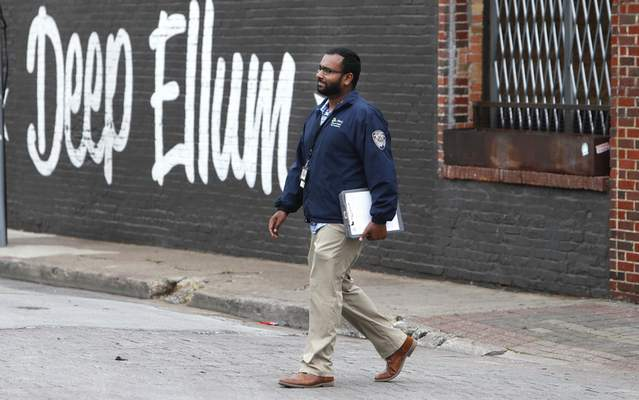 Associated Press Code compliance officer Eldho Babu checks on businesses this week amid concerns of COVID-19 spreading in the Deep Ellum section of Dallas.