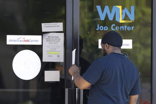Virus Outbreak Mississippi Unemployment Associated Press photos Tyrone Keoton Jr. is handed an unemployment benefit application form by a security guard behind the glass doors of a WIN Job Center in Jackson, Miss., on Thursday. (Rogelio V. SolisSTF)