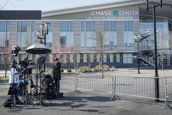 In this April 1, 2020, photo, a news crew wearing personal protective equipment due to COVID-19 concerns reports outside the Chase Center that will become a makeshift hospital at the USTA Billie Jean King National Tennis Center in the Queens borough of New York. (AP Photo/John Minchillo)