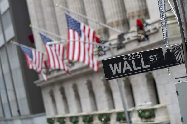 FILE - In this Jan. 3, 2020 file photo, the Wall St. street sign is framed by U.S. flags flying outside the New York Stock Exchange in New York. Global stocks are down, Friday, April 3, after the U.S. government said employers cut 701,000 jobs in March as they shut down or sharply curtailed business due to the coronavirus outbreak. (AP Photo/Mary Altaffer, File)