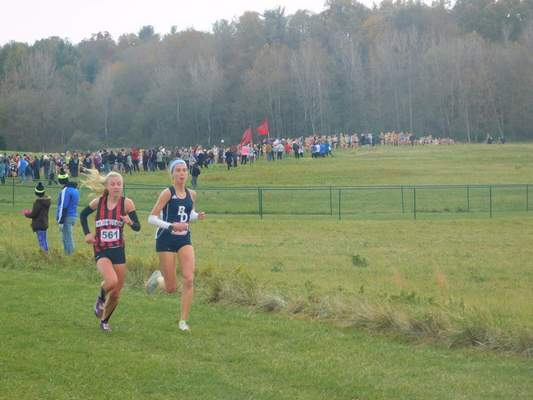 File photo  Erin Strzelecki of Bishop Dwenger, right, runs alongside Annalyssa Crain of Edgewood during the state cross country championship in November in Terre Haute. Strzelecki won the individual title in 17:22.9 and was named the 2019 Indiana Miss Cross Country on Friday.