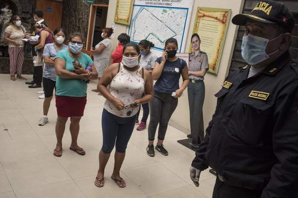 Associated Press Women in Peru detained for violating a national curfew listen to an officer Friday at a police station in Lima. The government is restricting movement by gender, with Friday designatedfor mento leave home to buynecessities.