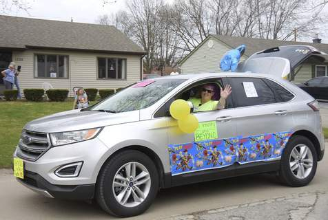 \Meadowbrook Home Association President Stacey McDaniel, who organized the parade, drives her car, decorated in a Toy Story theme, and waves at neighbors Saturday.