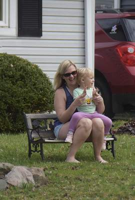 Katie Fyfe   The Journal Gazette Allyson Sauber and Ryla Pidgeon, 2, enjoy the Meadowbrook Pride Parade from their front yard in New Haven on Saturday.