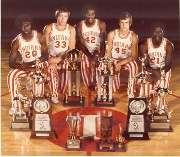 Indiana Athletics Indiana's 1976 senior class – from left, Bobby Wilkerson, Tom Abernathy, Scott May, Jim Crews and Quinn Buckner – poses with some of the hardware the team won that season, which ended in a national title.