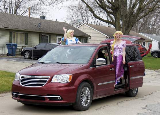 Katie Fyfe | The Journal Gazette  Residents dressed as Disney princesses wave to neighbors during the Meadowbrook Pride Parade in New Haven on Saturday.