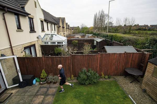 Jacob King/PA   Associated Press James Campbell runs a charity marathon to raise funds for the NHS, in his garden, while the country is in lockdown to control the spread of coronavirus, in Cheltenham, England, Wednesday. The former international athlete is spending his birthday running - in his seven-metre-long back garden - and will take over 7,000 shuttles back and forth to finish the 26.2-mile marathon.