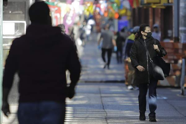 A woman wearing a mask walks on Roosevelt Avenue Saturday, April 4, 2020, in the Queens borough of New York. (AP Photo/Frank Franklin II)