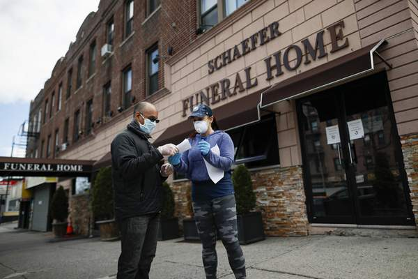 Employee Gina Hansen, right, hands documentation to a client outside Daniel J. Schaefer Funeral Home Thursday, April 2, 2020, in the Brooklyn borough of New York. (AP Photo/John Minchillo)