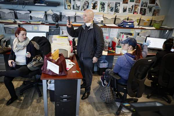Pat Marmo, owner of Daniel J. Schaefer Funeral Home, center, takes a phone call in his office while handling the overflow of clients stemming from COVID-19 deaths, Thursday, April 2, 2020, in the Brooklyn borough of New York. (AP Photo/John Minchillo)
