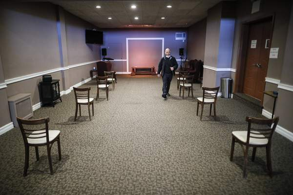 Pat Marmo, owner of Daniel J. Schaefer Funeral Home, walks through a viewing room set up to respect social distancing, Thursday, April 2, 2020, in the Brooklyn borough of New York. (AP Photo/John Minchillo)