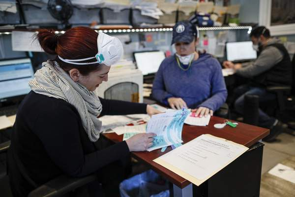 Employee Elysia Smith works through a stack of papers each denoting a body requiring retrieval from a hospital at Daniel J. Schaefer Funeral Home, Thursday, April 2, 2020, in the Brooklyn borough of New York. (AP Photo/John Minchillo)
