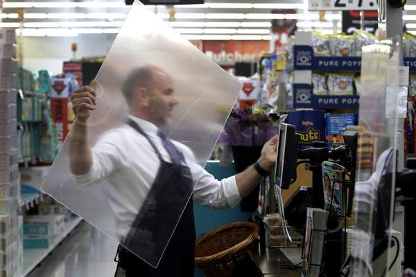 FILE - In this March 26, 2020, file photo, Dave Herrick installs a plexiglass panel at a checkout lane at a Hy-Vee grocery store in Overland Park, Kan. (AP Photo/Charlie Riedel, File)