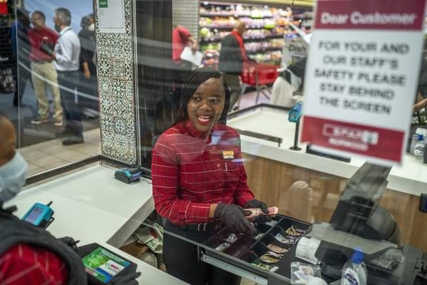In this March 30, 2020, photo, Zandile Mlotshwa, 21, cashier at Spar supermarket in the Norwood suburb of Johannesburg, counts her cash at the end of her shift. (AP Photo/Jerome Delay)