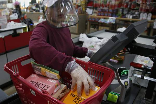 FILE - In this March 27, 2020, file photo, cashier Baby San wears a face shield and gloves as she scans items at grocery store Super Cao Nguyen, in Oklahoma City, due to concerns over the COVID-19 virus. (AP Photo/Sue Ogrocki, File)