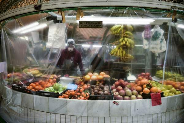FILE - In this April 2, 2020, file photo, a worker wearing a face mask stands inside of a stall covered with a piece of plastic to prevent the spread of coronavirus, at a market in Pamplona, northern Spain. (AP Photo/Alvaro Barrientos, File)