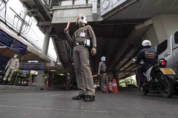Policemen wearing face masks to protect themselves from the new coronavirus at a health checkpoint in Bangkok, Thailand, Friday, April 3, 2020. (AP Photo/Sakchai Lalit)