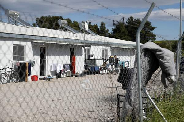 Migrants gather outside their container houses during a quarantine against coronavirus at a refugee camp in Ritsona about 80 kilometers (50 miles) north of Athens, Thursday, April 2, 2020. (AP Photo/Thanassis Stavrakis)