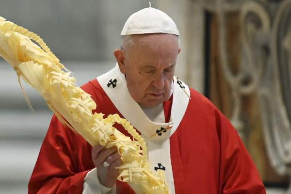 Pope Francis holds a palm branch as he celebrates Palm Sunday Mass behind closed doors in St. Peter's Basilica, at the Vatican, Sunday, April 5, 2020, during the lockdown aimed at curbing the spread of the COVID-19 infection, caused by the novel coronavirus. (AP Photo/pool/Alberto Pizzoli)