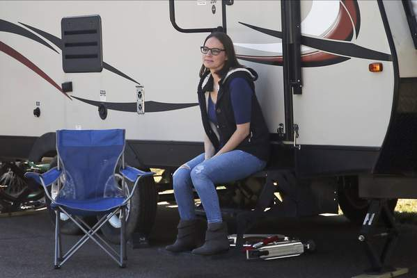 Associated Press  ICU nurse Lisa Neuburger poses by the camper she is living in parked in her former in-laws' driveway in St. Paul Park, Minn.