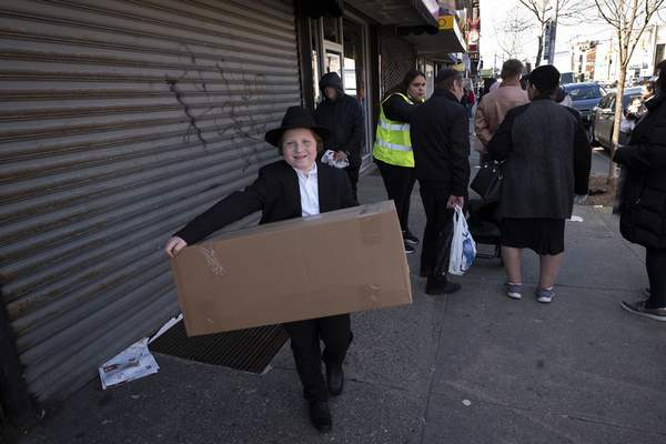 Associated Press Aboy carries a box of matzos for Passover that he picked up from his synagogue in the Brooklyn borough of New York.