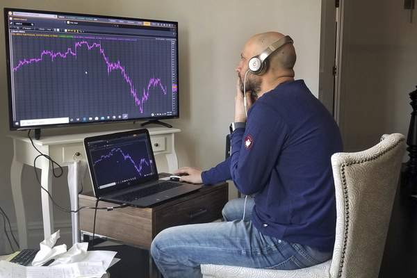 In this image provided by Meric Greenbaum, Greenbaum, a Designated Market Maker with IMC, who normally works on the New York Stock Exchange trading floor, works in his home office in Shelter Island, NY, Monday, April 6, 2020. Stocks around the world jumped Monday after some of the hardest-hit areas offered sparks of hope that the worst of the coronavirus outbreak may be on the horizon. (Lucas Greenbaum/Courtesy Meric Greenbaum via AP)