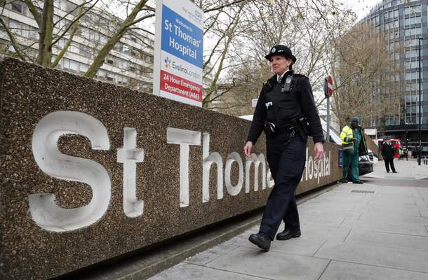 A police officer patrols outside a hospital where it is believed but not confirmed that Britain's Prime Minister Boris Johnson is undergoing tests after suffering from coronavirus symptoms, in London, Monday, April 6, 2020. British Prime Minister Boris Johnson has been admitted to a hospital with the coronavirus. Johnson's office says he is being admitted for tests because he still has symptoms 10 days after testing positive for the virus. (AP Photo/Frank Augstein)