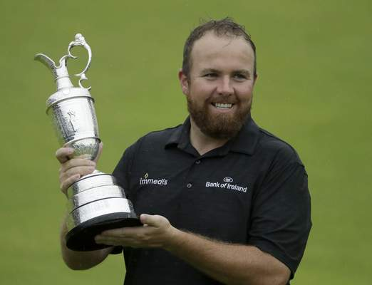 FILE - In this Sunday, July 21, 2019 file photo Ireland's Shane Lowry holds the Claret Jug trophy on the 18th green as he poses for the crowd and media after winning the British Open Golf Championships at Royal Portrush in Northern Ireland. The organizers of the British Open announced Monday April 6, 2020, that they have decided to cancel the event in 2020 due to the current Covid-19 pandemic and that the Championship will next be played at Royal St George's in 2021. (AP Photo/Matt Dunham)