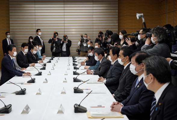 Japanese Prime Minister Shinzo Abe, left, speaks during a meeting of the headquarters for measures against the coronavirus disease at the prime minister official residence in Tokyo, Japan, Monday, April 6, 2020. (Franck Robichon/Pool Photo via AP)