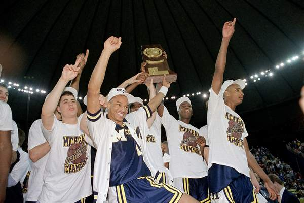 FILE - In this April 4, 1989, file photo, Michigan basketball players celebrate with the national championship trophy after defeating Seton Hall 80-79 in the NCAA college basketball Final Four final game in Seattle. (AP Photo/Bob Jordan, File)