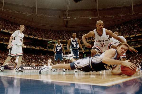 FILE - In this March 29, 1999, file photo, Duke's Chris Burgess tries to keep the ball from going out of bounds as Connecticut's Edmund Saunders (51) watches in the first half of the championship game of the NCAA college basketball Final Four, in St. Petersburg, Fla. UConn won 77-74. (AP Photo/Dave Martin, File)